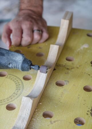 Close-up of a man sanding curves to a smooth finish with a dremel on a plank of wood held on a workbench, to make a wine rack  Stock Photo