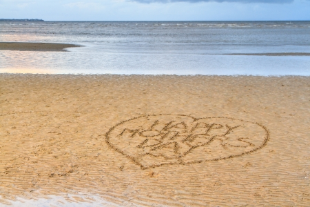 Happy Mother Day written in a love heart, in the sand on a flat beach  A calm blue sea fills the background