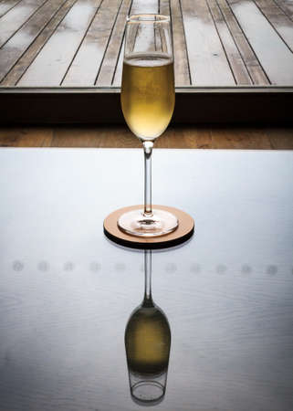 A single Champagne glass sits on a highly polished table, which shows the reflection