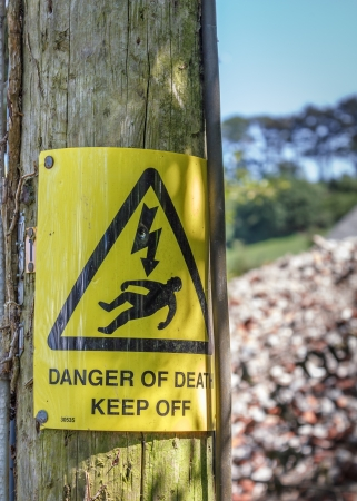 electrocution: A yellow  Danger of Death   Keep Off  warning sign typical in the UK   Nailed to an wooden utility pole in the countryside