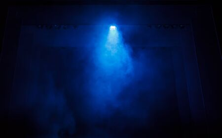 Smoke creates a misty haze in front of a blue light, on a dark stage  Stock Photo