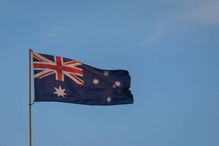 The Australian Flag flying high from a flagpole, tinged ever so slightly pink by the dusky sunset colours, against a blue sky