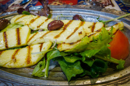 haloumi: Tasty grilled halloumi salad with green lettuce and ripe red tomato, garnished with a black olive