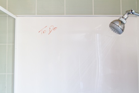 A running shower with a blank white wall, with  To do  written in crayon photo