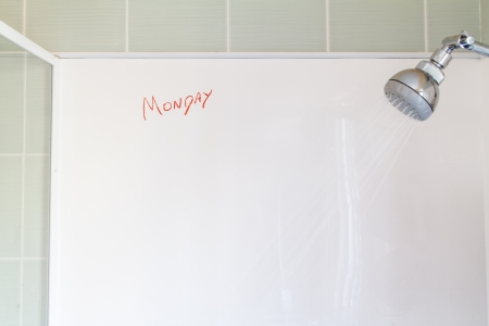 A running shower with a white blank wall, with  Monday  written in red crayon photo
