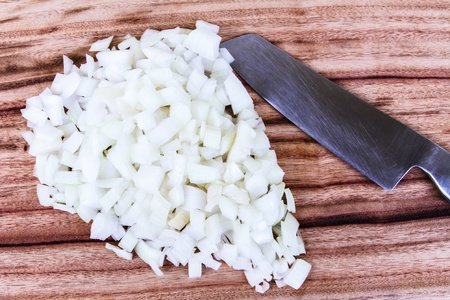 Freshly chopped white onion with the chopping knife, on a wooden chopping board