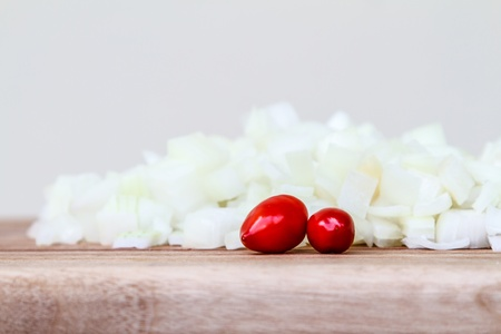 Side view of freshly chopped white onion, garnished with two fresh red chillies, on a wooden chopping board