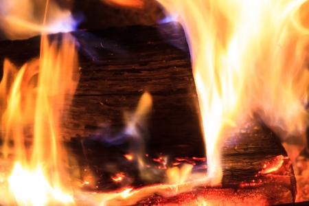 Macro close up of the end of a burning log surrounded with white hot blue flames and glowing orange embers photo