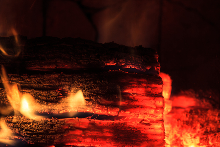 A blackened log glowing red hot inside a modern fireplace, with small orange flames photo