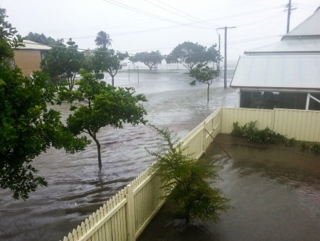 Flood waters running across the street and into the gardens of homes in Sandgate Stock Photo