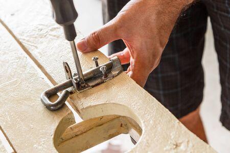 screwing: CLose up of a man screwing a screw into a bolt lock on a gate   Screwdriver is still