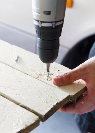ドリルがこの典型的な DIY のガレージで塗られた木にねじを掘削男のクローズ アップの回転します。