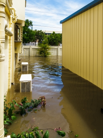 View down the side of a house during Brisbane floods   Air-conditioning units and garage are in water