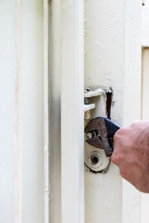 Man using a wrench to tighten a bolt on the hinge of a gate Stock Photo