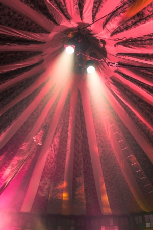 Two bright spotlights under a red stripey circus tent, vertical