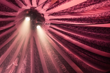 Two spotlights shining down under a red stripey circus tent photo