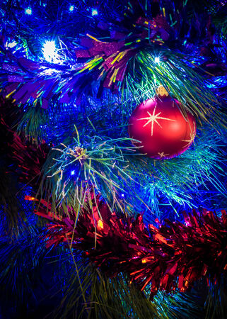 Close up of a brightly decorated Christmas tree, with glittering tinsel, shiny red ball, and fairy lights photo