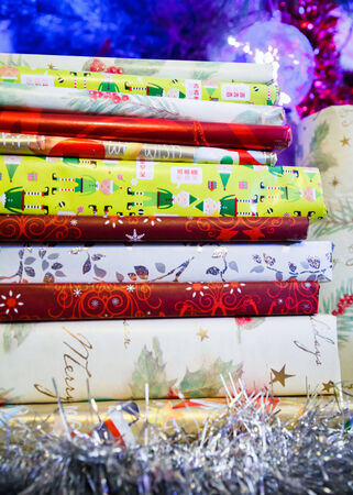 Pile of books wrapped in Christmas wrapping paper under a Christmas tree with tinsel photo