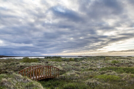 Curved wooden bridge on a windswept north Iceland moor, under grey clouds as the sun sets photo