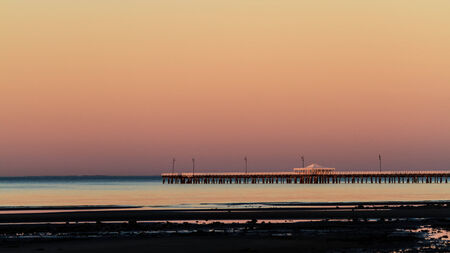 The historic Shorncliffe Pier in Brisbane, lit by the pink light of late dusk at sunset