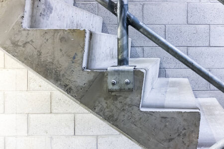 Side view of a set of concrete stairs, with a breeze block wall in the background