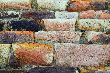 decades: Colourful sandstone sea wall with lots of orange, pink, beige, purple and black colours.  The bricks are laid horizontally and have been weathered over decades by the sea Stock Photo