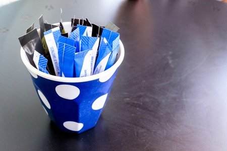 Blue and white paper sachets of artificial sweetener in a blue and white spotted cup on a table.