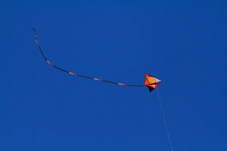 Kite flying high in the deep blue sky with the tail flicking up
