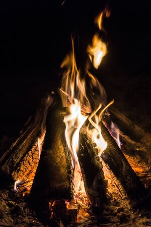 Camp fire burning, with the wooden logs in a typical triangle teepee position, and flames reaching up into the black sky.