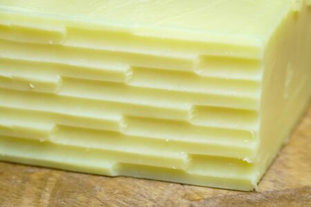 Close up of the corner of a block of cheddar cheese which has been grated, on a wooden cutting board Stock Photo
