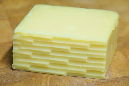 A block of cheddar cheese with lines from a grater angled on a wooden board.