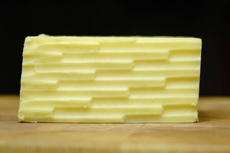 Straight on look at a block of cheddar cheese with a lined pattern from a grater, on a wooden cutting board. Stock Photo