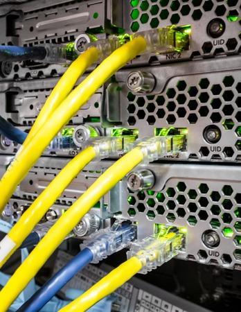 Ethernet cables plugged into the back of a computer blade array with green activity lights.