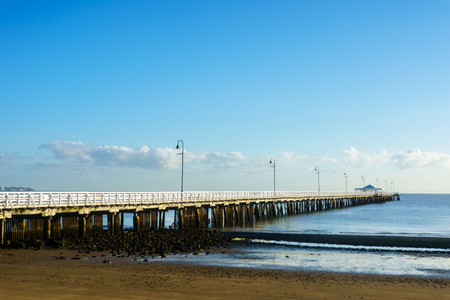 Shorncliffe Pier in early morning sun under a blue sky.  The wooden jetty is stretching out into the blue sea of Moreton Bay.  Brisbane, Australia. Stock Photo