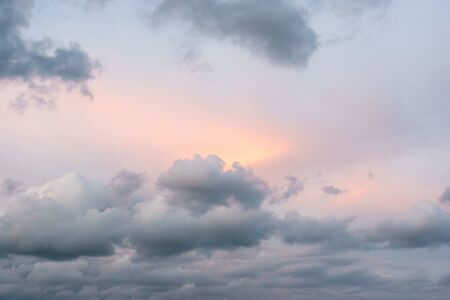 Ray of warm orange and pink sunlight bursting through grey clouds. Very pretty pastel colours. Stock Photo