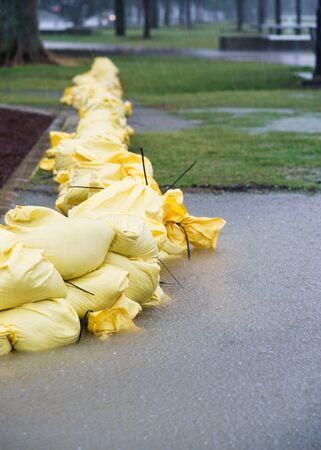 Yellow sandbags lined up to protect a park from heavy rain and flood water.  Flooding has starting and it is raining hard. Sandgate, Brisbane, Queensland, Australia. Stock Photo