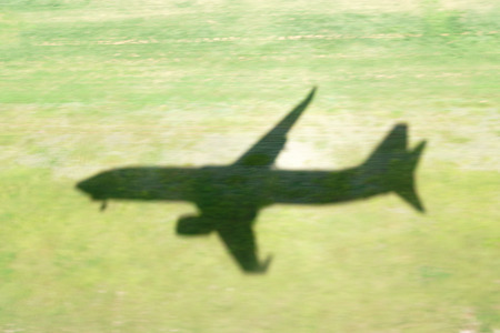 Shadow of an airplane Boeing 737-800 landing over a mowed grass field.  The landing gear is down. Stock Photo