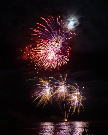 Final fireworks of the Bluewater Festival firework display 2015, in Bramble Bay.  The full moon also made an appearance through the clouds. Bursts of  pink and purple crysanthemum fireworks in the air Stock Photo