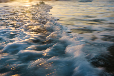 Close up of an ocean wave rushing to the beach, with the early morning sun low on the horizon.  The warm yellow sunlight is catching the sea spray off the wave. Stock Photo