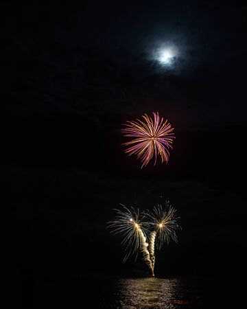 Pink and yellow chrysanthemum firework over green and gold spiral fountain of sparks. The moon is visible through the clouds overhead. Stock Photo