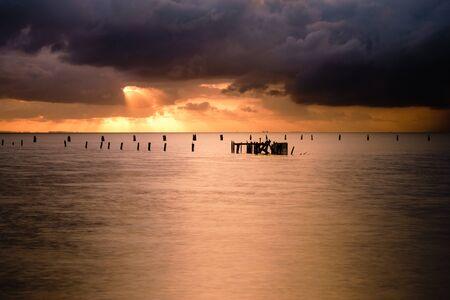 Shaft of orange dawn sunlight breaking through the grey storm clouds.  Below is the remnants of the Shorncliffe Pier in silhouette. Sandgate, Brisbane, Queensland, Australia.
