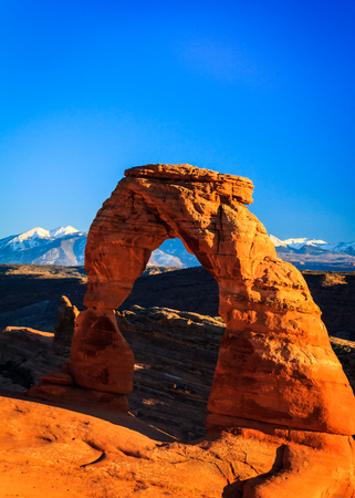 Delicate Arch in the Arches National Park lit by the late afternoon sun under a clear blue sky.  The snowcapped La Salle mountains