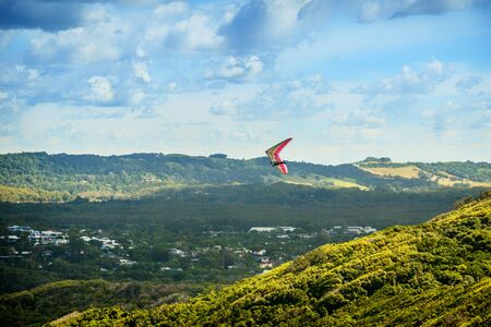 Hang glider flying over the valley in Bryon Bay New South Wales Australia Stock Photo