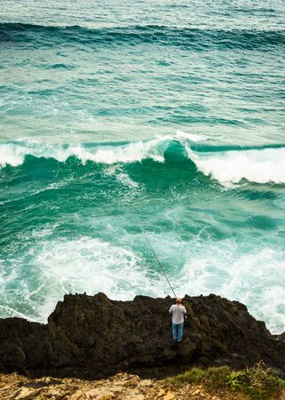 Single fisherman rock fishing on the cost of Byron Bay with a large wave breaking. Stock Photo