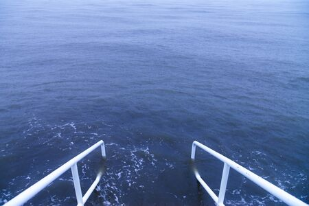 White handrails alongside steps that lead into a blue stormy sea. Stock Photo