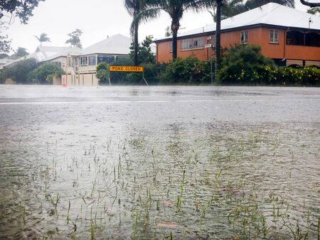 Road Closed sign at the end of a flooded street in Brisbane Australia.  In the foreground in a large flood puddle with grass and raindrops. Stock Photo
