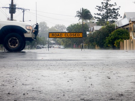Road Closed sign on a flooded road.  Cars are doing uturns in the background.  The front of a moving 4wd car is visible.  In the foreground is a floodwater puddle with raindrops.