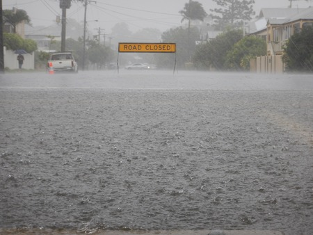 дождь: Дорога закрыта знак на затопленной улице в сильный дождь. В forground огромный паводковыми водами лужа с тяжелыми каплями дождя.