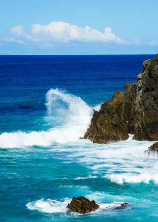 Wave from the deep blue Pacific Ocean crashing onto the cliffs at Byron Bay in New South Wales Australia.