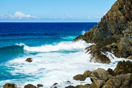 Waves crashing onto the jagged rocks at the base of the cliff at Byron Bay.  The ocean is a deep blue colour with turquoise where the waves are breaking.  Taken in New South Wales Australia.
